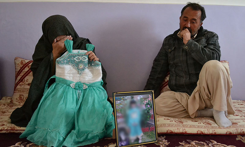 The parents of Sahar Batool, who was from the minority Hazara ethnic group and found dead at a garbage dump, mourn while holding their late daughter's dress in Quetta on November 7, 2014. -AFP photo