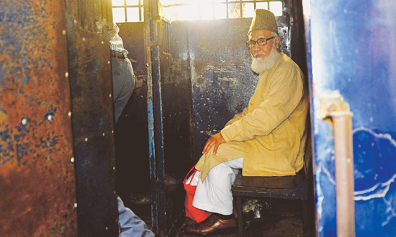 JAMAAT'S supreme leader Motiur Rahman Nizami sits inside a prison van following his sentencing at a court in Chittagong.—AFP