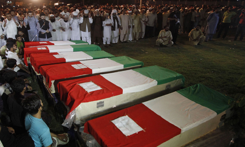 Supporters of preacher Tahir-ul-Qadri perform funeral prayers over coffins of fellow supporters killed during clashes with police in Lahore on late June 17, 2014 - AFP/File