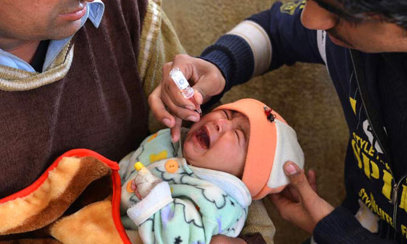 A polio worker gives vaccine to a young girl. — AFP/File