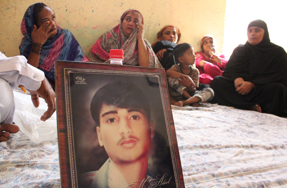 Bereaved mothers wipe away tears behind the portrait of Adeel, a victim of the fire. Photo by Danyal Adam Khan