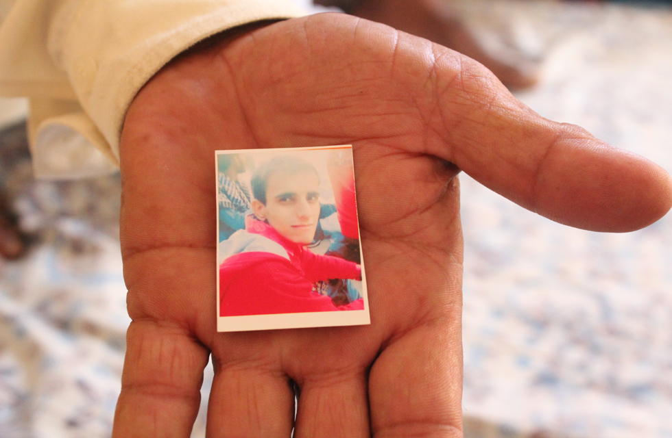 Muhammad Jabbir, the head of a recently-formed committee of the victims' families, holds a photo of his 22-year-old son, Jahanzaib, who lost his life in the incident. Photo by Danyal Adam Khan