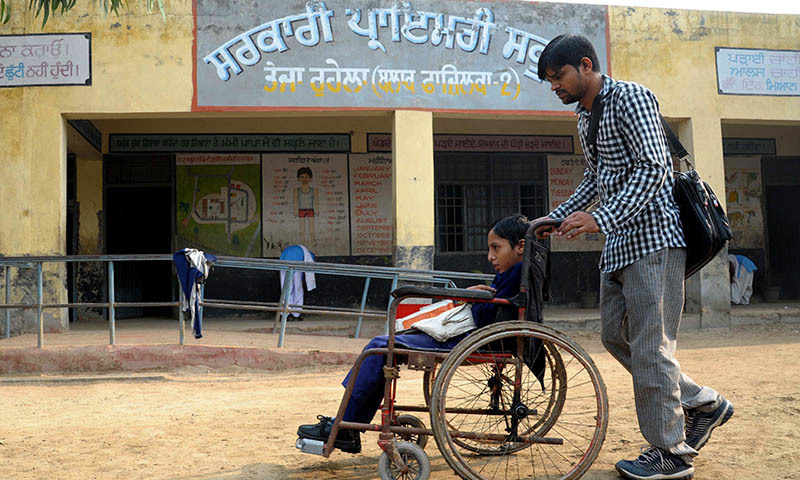 In this photograph taken on October 30, 2014, disabled Indian school student Gurcharan Singh is pushed on her wheelchair towards school  in the village of Teja Ruhela, close to the Indian-Pakistan border some 17kms from Fazilka in the northern state of Punjab. -AFP