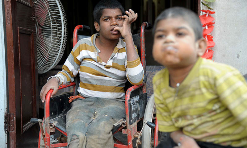 In this photograph taken on October 30, 2014, disabled Indian children fifteen year old Poonam (L)and her sister Renu sit at their home in the village of Teja Ruhela, close to the Indian-Pakistan border some 17kms from Fazilka in the northern state of Punjab.  - AFP