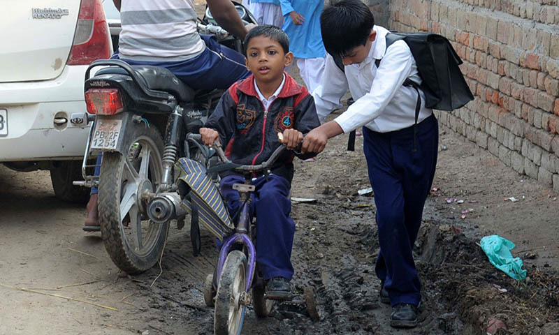 In this photograph taken on October 30, 2014, disabled disabled Indian school student Jasan Singh (C) is pushed on his bicycle by his friend Vikram towards school in the village of Teja Ruhela, close to the Indian-Pakistan border some 17kms from Fazilka in the northern state of Punjab.  - AFP
