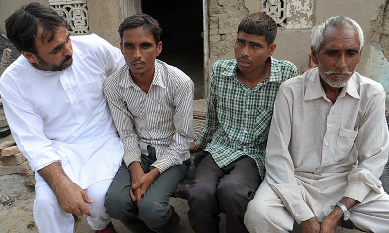 In this photograph taken on October 30, 2014, Indian comedian and the Member of Parliament Bhagwant Mann (L) speaks with residents Shankar Singh (2L) and his brother Visakha Singh (2R) who have lost their eyesight, as their father Mohinder Singh (R) looks on in the village of Teja Ruhela on the Indian-Pakistan border some 17kms from Fazilka in the northern state of Punjab. - AFP