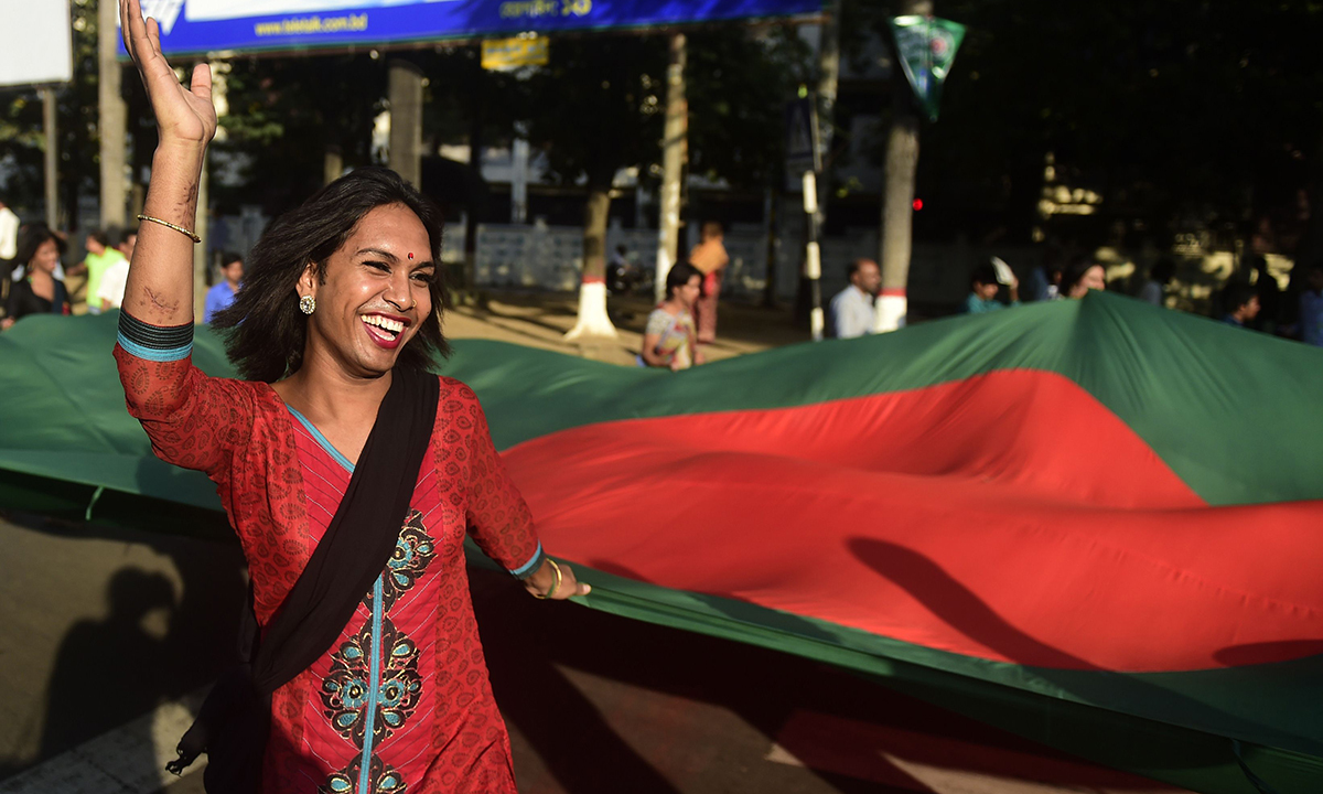 Transgenders hold the country's national flag.— AFP Photo