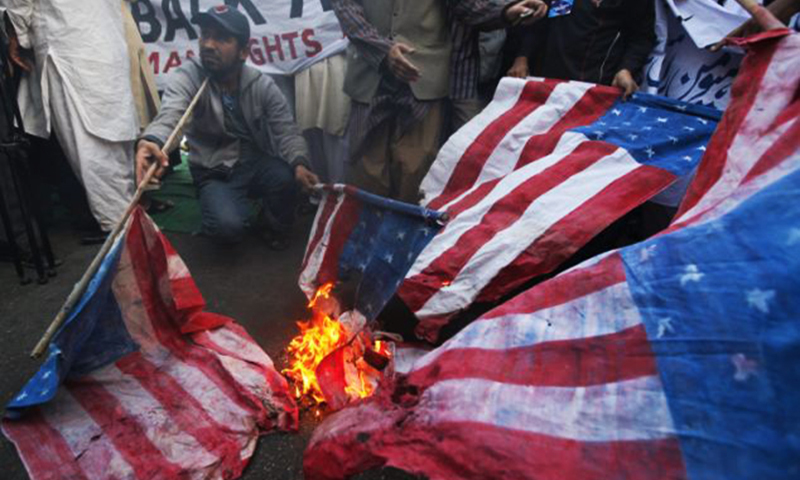 Activists set fire to American flags at a protest rally of a religious party in Lahore (2012).