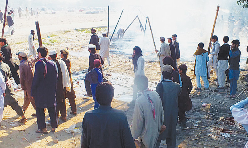 BANNU: IDPs of North Waziristan Agency carrying batons demonstrate after a clash with police at a ration centre here on Thursday.—Online