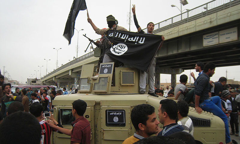 In this March 30, 2014 photo, Islamic State militants wave Al Qaeda flags as they patrol in a commandeered Iraqi military vehicle in Fallujah, 40 miles west of Baghdad. — AP