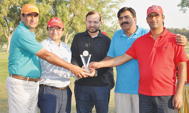 RAHIM YAR KHAN: FFC general manager plant Naveed Ahmed Khan gives the winners' trophy to members of the Sona Golf Club team.