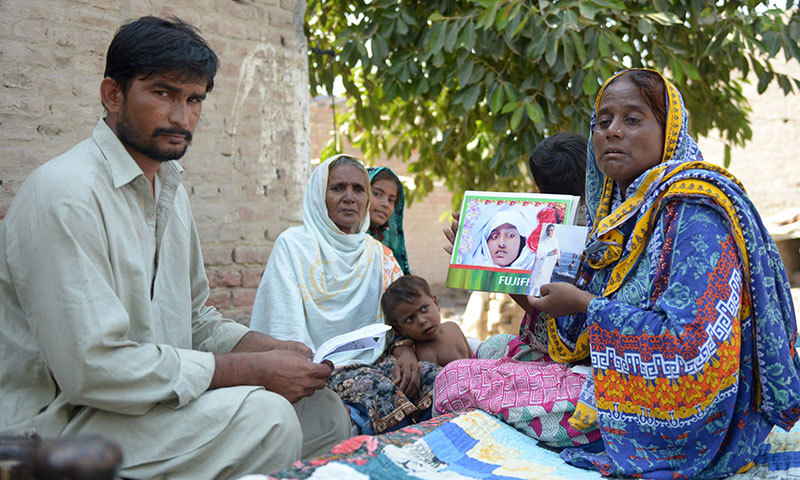 "Razia Shaikh, one of countless mothers to suffer the misery of ""karo kari"", shows a photograph of her daughter during an interview with AFP in Sukkur. — AFP"