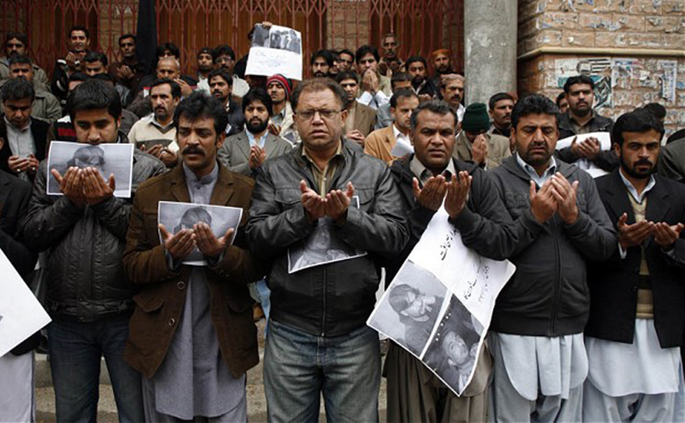 Members of the Balochistan Union of Journalists pray for Imran Sheikh – a journalist killed in a bomb blast – outside the Quetta Press Club. — Reuters