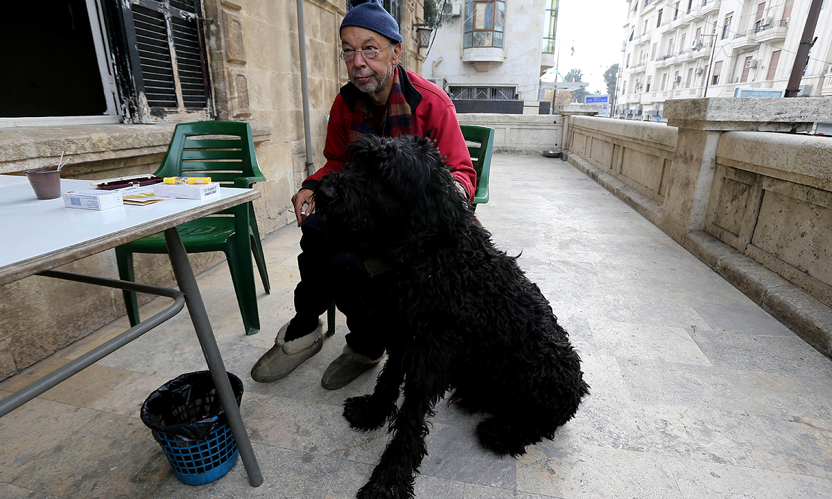 Armen Mazloumian, the owner of the Baron Hotel, the oldest hotel in Syria's Aleppo, sits at the terrace with his black Russian Terrier. —AFP