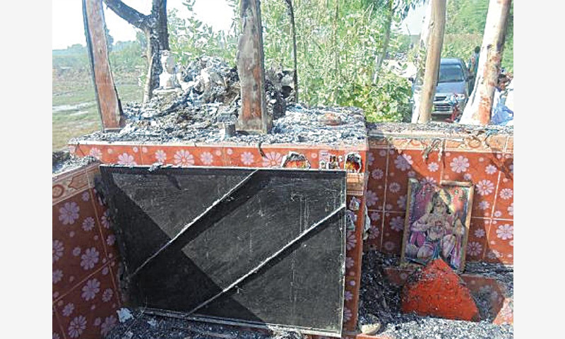 Ash is scattered round a barely visible idol on the raised platform and the floor of the small temple which was torched in Tando Mohammad Khan in the early hours of Friday.—Dawn