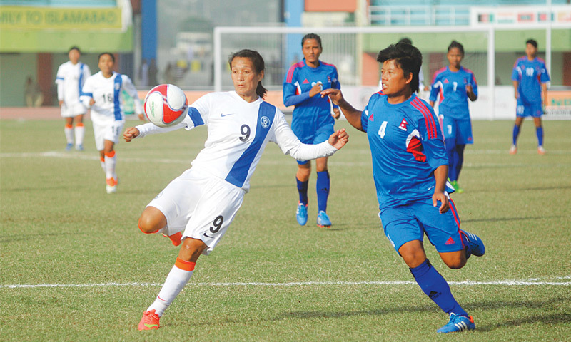 ISLAMABAD Indian and Nepal players fight for the ball during the SAFF Women's Championship final here at the Jinnah Stadium on Friday.—Tanveer Shahzad / White Star