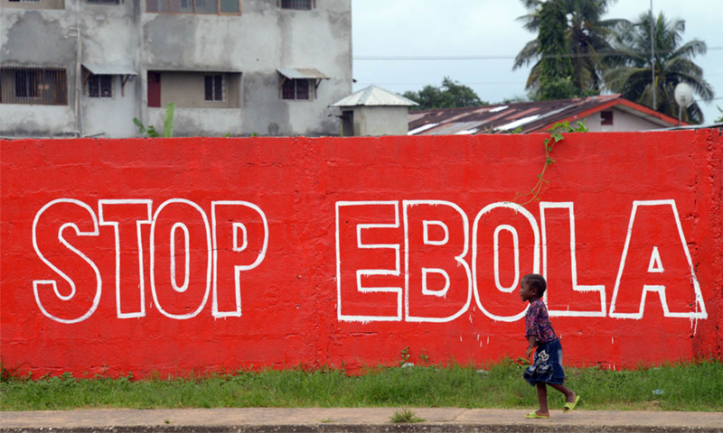 "A girl walks past a slogan painted on a wall reading ""Stop Ebola"" in Monrovia, Liberia – AFP/ File"