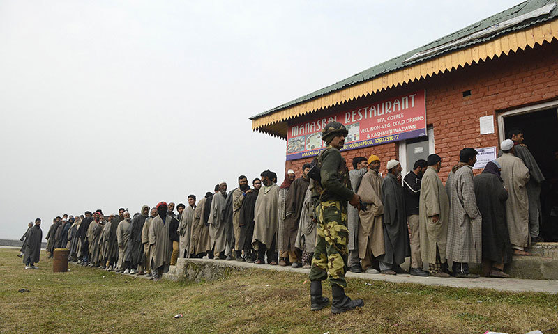 An Indian Border Security Force soldier stands guard as Kashmiri muslim voters queue outside a polling station at Manasbal. — AFP