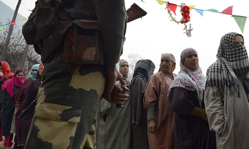 An Indian Border Security Force soldier stands guard as Kashmiri muslim voters queue outside a polling station at Manasbal, about 20 kms from the capital Srinagar. — AFP
