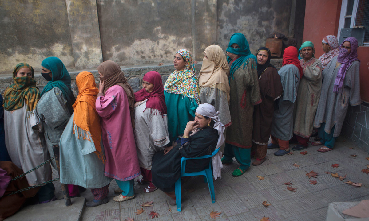 Kashmiri women wait in a queue to cast their votes.  — Photo by AP