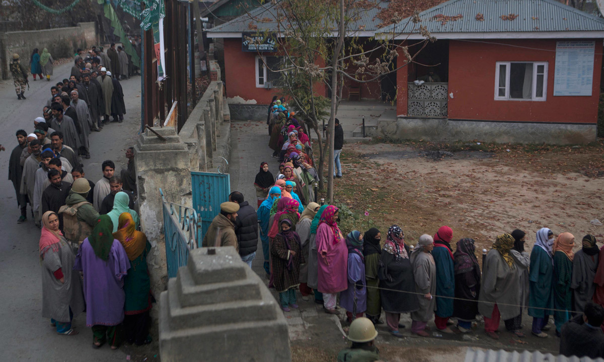 Kashmiris stand in queue to cast their votes outside a polling station. — Photo by AP