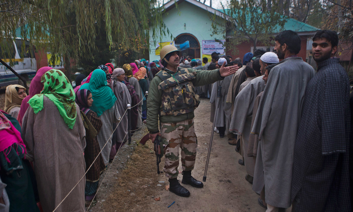 An Indian paramilitary soldier asks Kashmiri voters to stand in queue as they wait outside a polling station.  — Photo by AP
