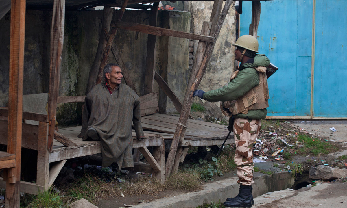 An Indian paramilitary soldier asks a Kashmiri voter to join others in a queue as he sits outside a polling station. — Photo by AP