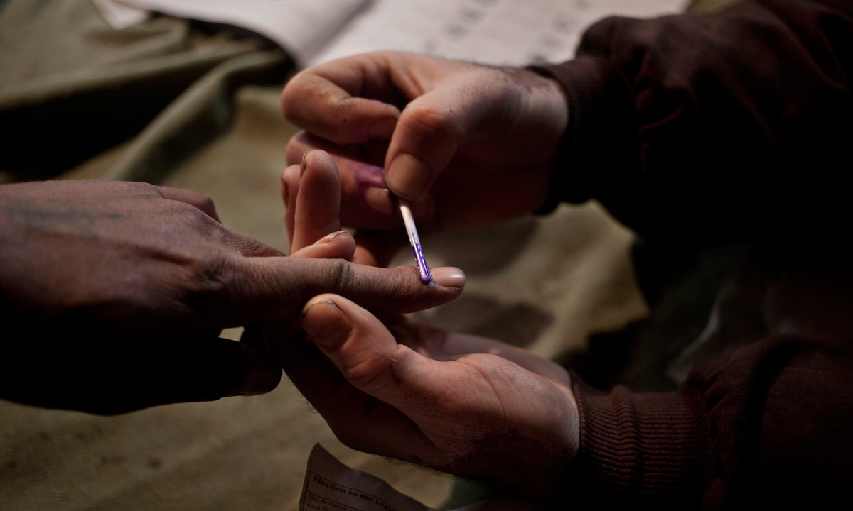 A polling officer (R) puts an ink mark on the finger of a voter. — Photo by AP