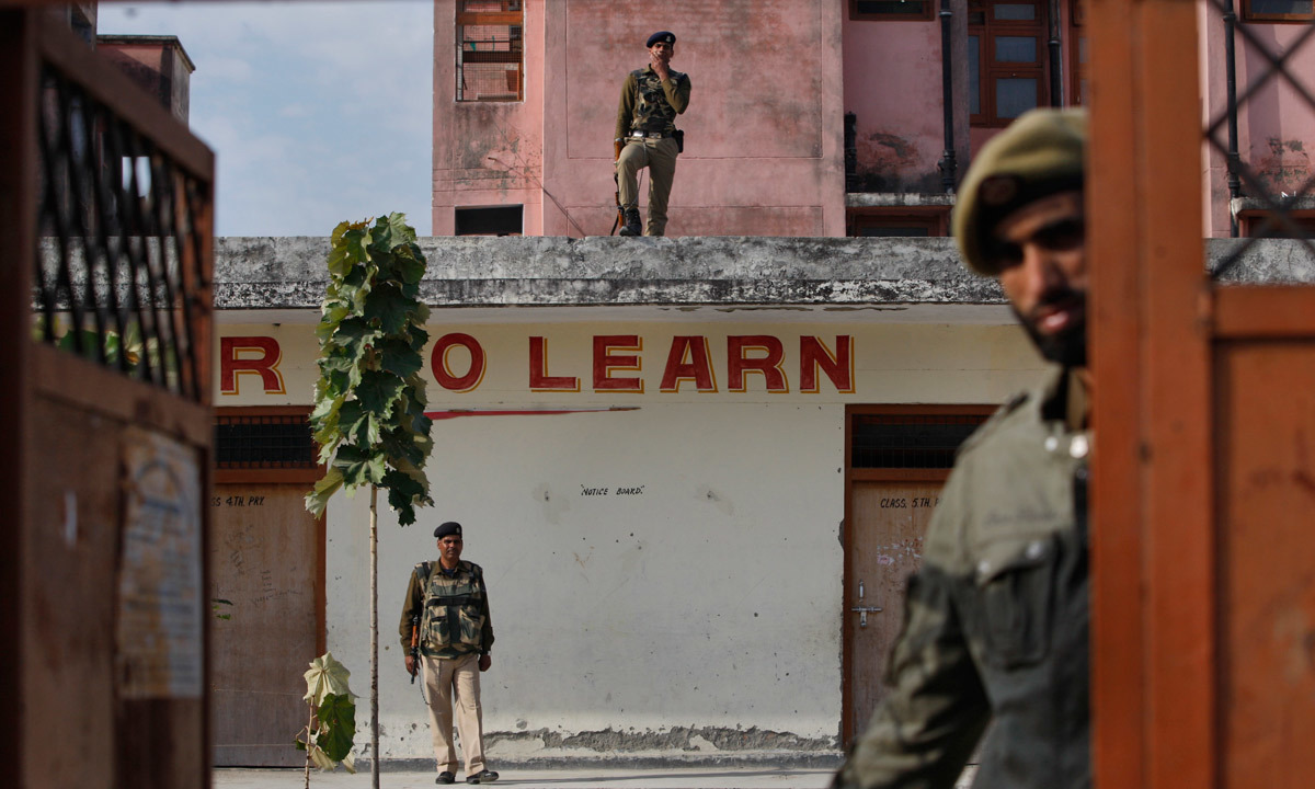 Indian paramilitary soldiers guard a polling booth set up for migrant Kashmiris. — Photo by AP