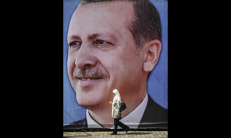 A file picture taken on August 8, 2014 shows a woman walking past a campaign poster of Turkish Prime minister Recep Tayyip Erdogan in Istanbul. —AFP