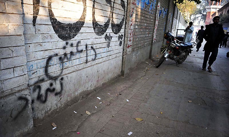 A pedestrian walks past wall graffiti which reads Daish, the arabic acronym for Islamic State (IS), in Peshawar on November 22, 2014.- AFP/file