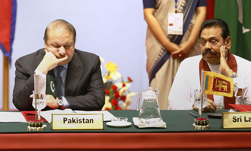 Nawaz Sharif (L) and the President of Sri Lanka Mahinda Rajapaksa (R) look on during the opening session.- AFP photo