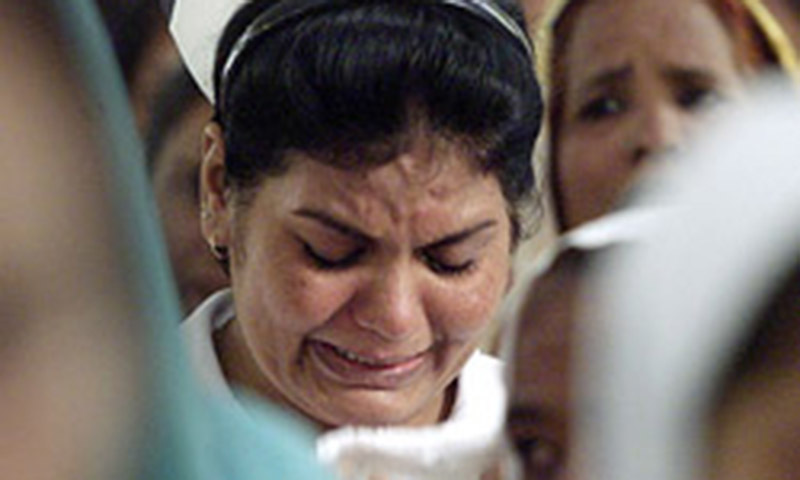 A nurse cries during a sombre memorial service to mourn the death of four nurses killed outside the building. Reuters/File
