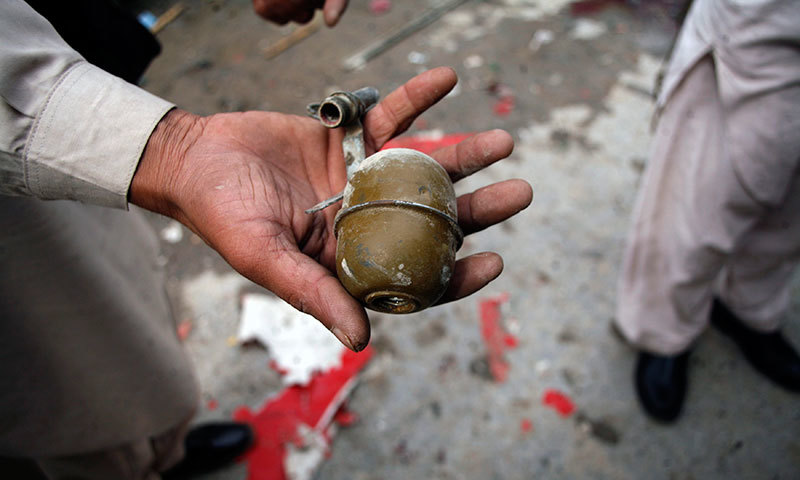 A security official shows a detonated grenade found at the site of a bomb attack in Pakistan. – Reuters/File