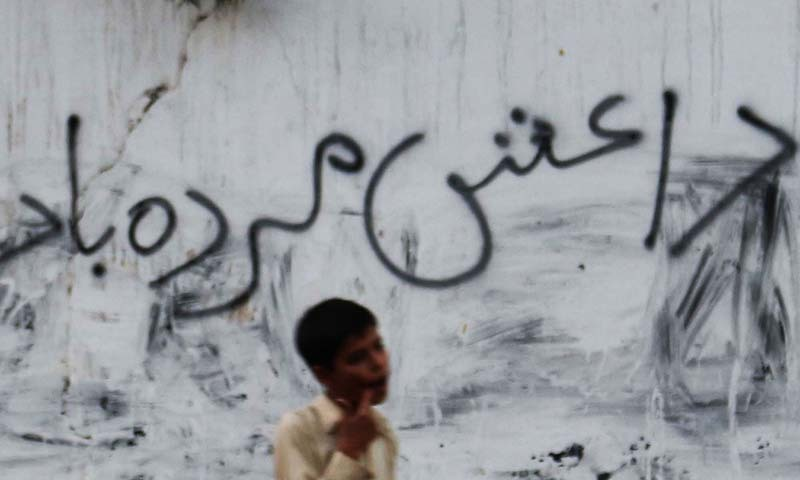 Man passing  near a wall on which anti Islamic State  (ISIS) slogan in written, at M.R Kyani Road in Karachi. - PPI