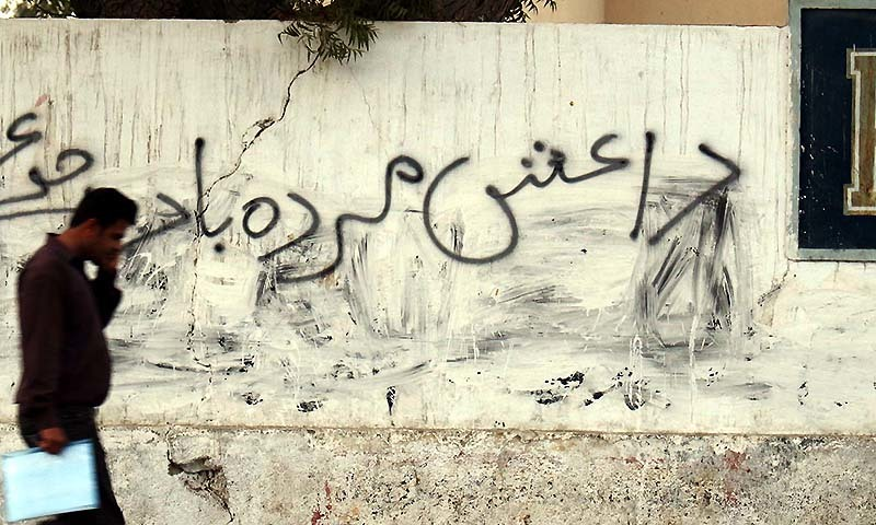 A man passes a wall on which an anti Islamic State  (ISIS) slogan is written, at M.R Kyani Road in Karachi. - PPI