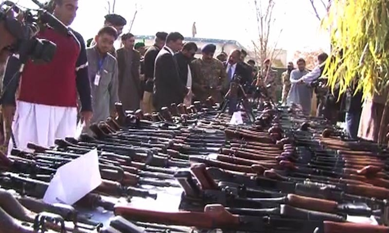 Mediapersons inspect the displayed weapons seized by security forces during raids in several parts of Balochistan. — DawnNews screengrab