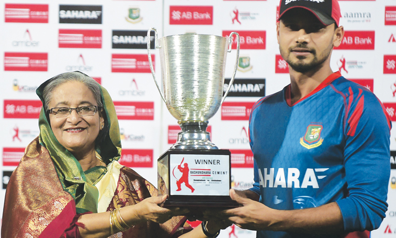 Bangladesh Prime Minister Sheikh Hasina and national team captain Mashrafe Bin Mortaza pose for a photograph with the series trophy after the fifth ODI against Zimbabwe at the Sher-e Bangla National Stadium on Monday.—AFP