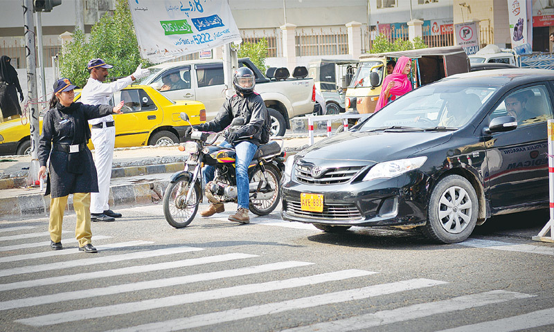 Police constable Mehwish Dani on Tuesday asks drivers to stay behind the zebra crossing while stopping at the red light.—Fahim Siddiqi / White Star