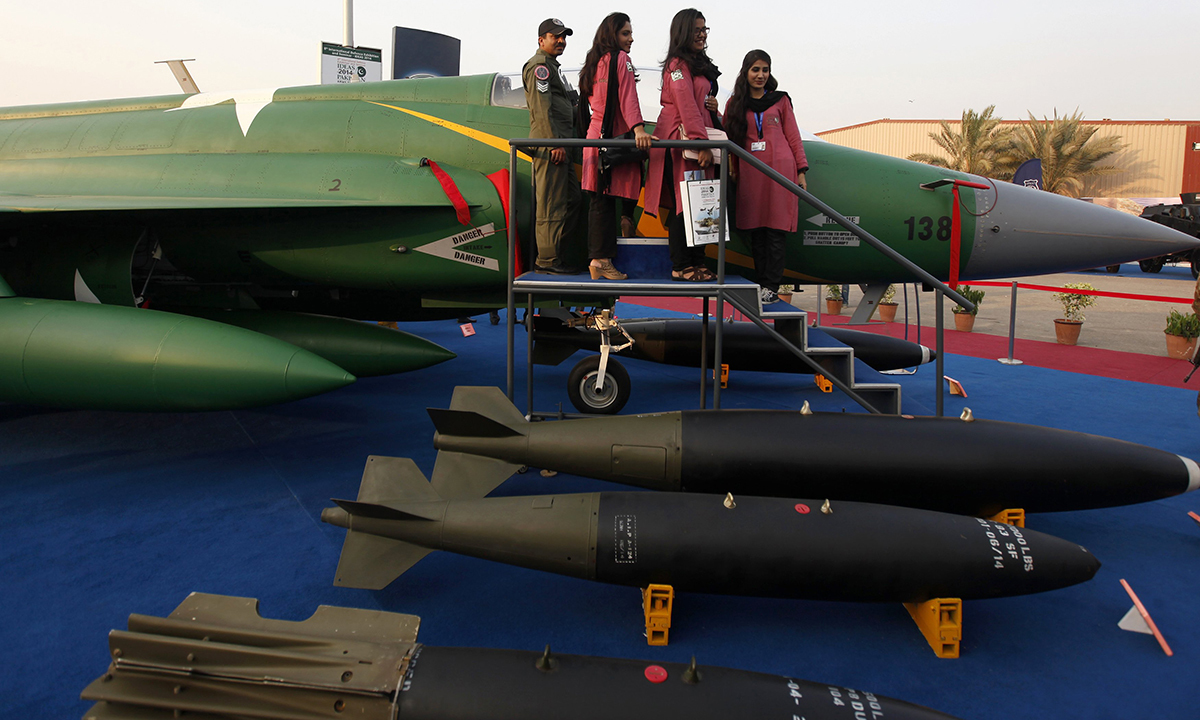 """Visitors stand next to the JF-17 Thunder fighter jet during the International Defence Exhibition and Seminar """"Ideas 2014"""" in Karachi December 2, 2014. — Reuters"""