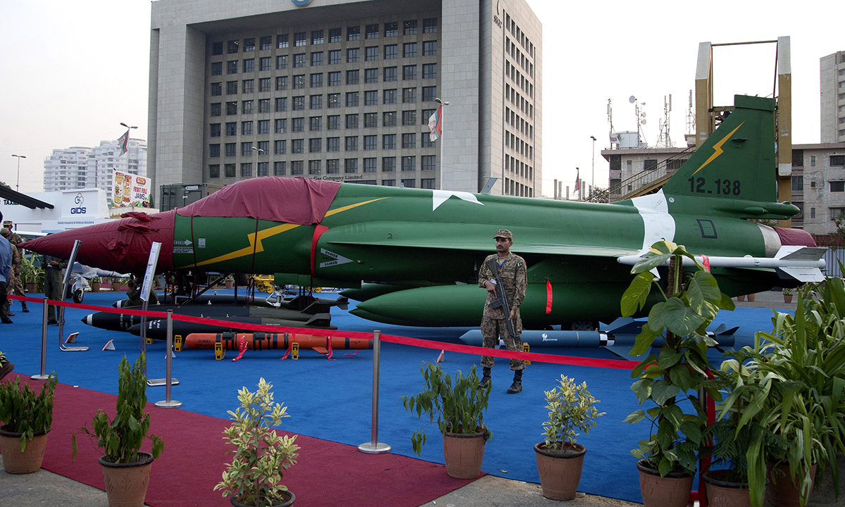 A Pakistan army soldier stands guard near a combat aircraft, jointly developed by China and Pakistan, displayed at Ideas 2014, in Karachi. — AP