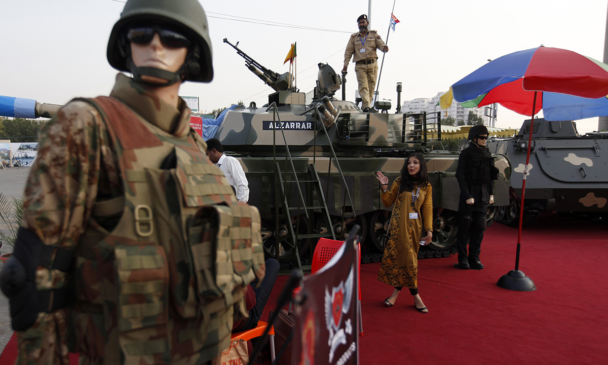 A visitor stands next to armoured mannequins in front of a Pakistani tank Al-Zarrar on display. — Reuters