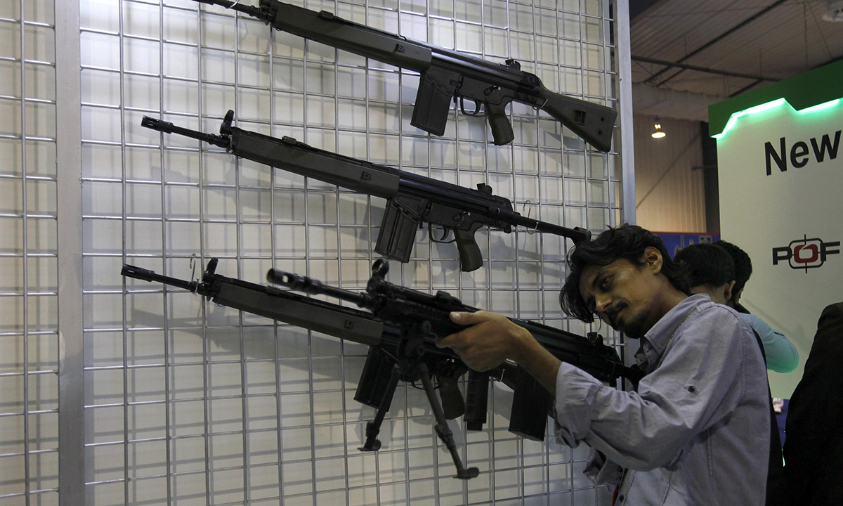 A visitor checks a rifle on display. — Reuters