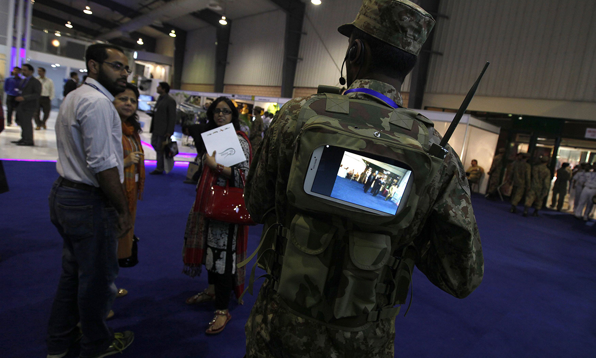 A soldier (R) with a monitor mounted on his back, linked to a camera on a gun (unseen), is shown to visitors during the International Defence Exhibition and Seminar. — Reuters