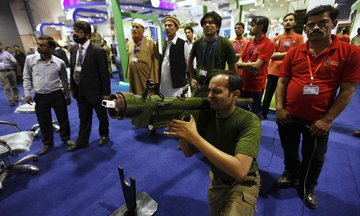 A visitor points a rocket launcher, attached with a laser censor, as he takes aim at a target. — Reuters