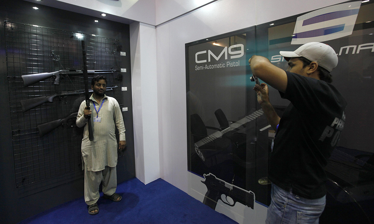 A visitor poses with a rifle on display for a photograph. — Reuters