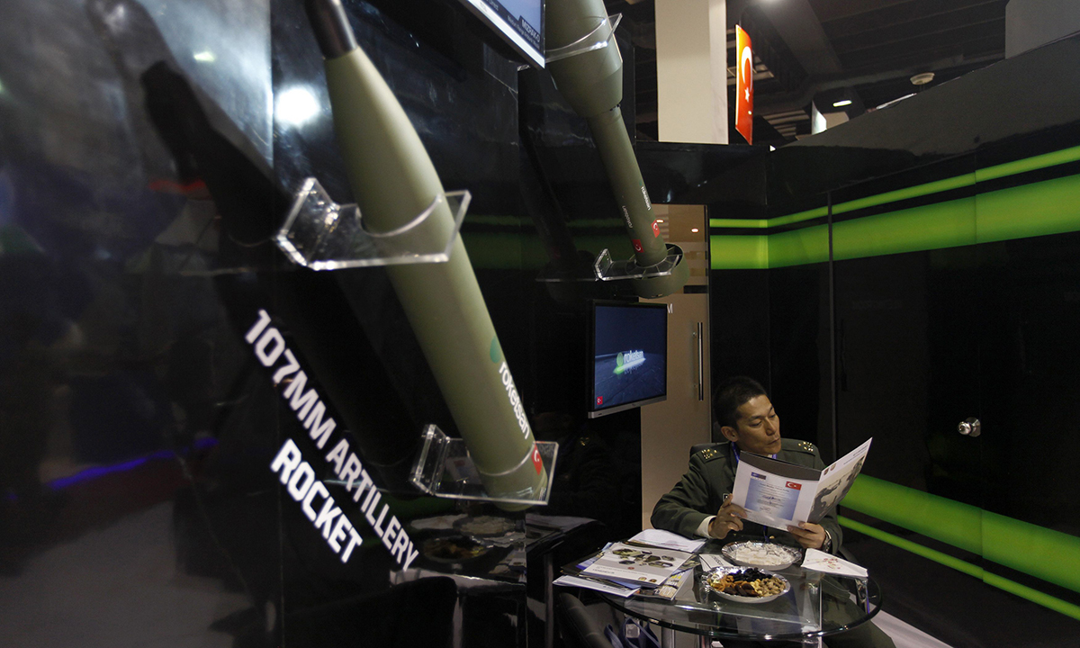 A foreign visitor reads a brochure while sitting at a booth displaying rockets. — Reuters