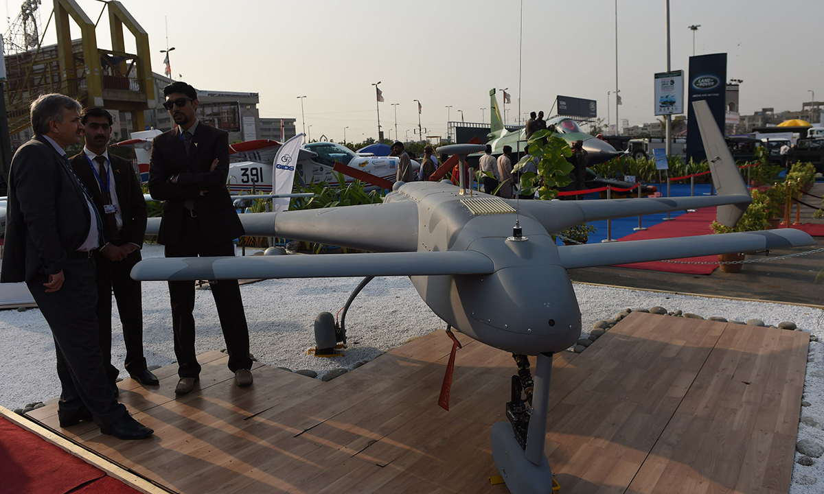 Visitors look at a model of a Pakistan-made unmanned aircraft, or drone. — AFP