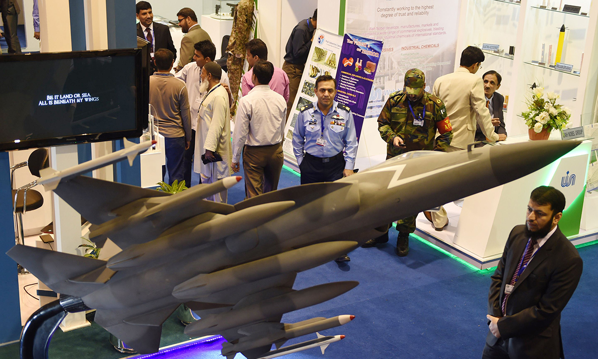 Visitors walk past a model of a PAC JF-17 Thunder multirole combat aircraft. — AFP