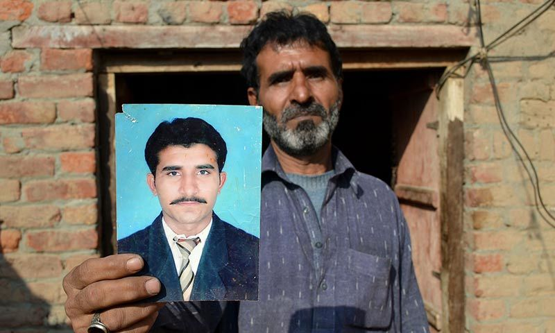 The father of Mohammad Irfan, who was sentenced to death for drug trafficking in Saudi Ariabia, Haji Abdul Haq, poses with a picture of his son in Sargodha. — AFP